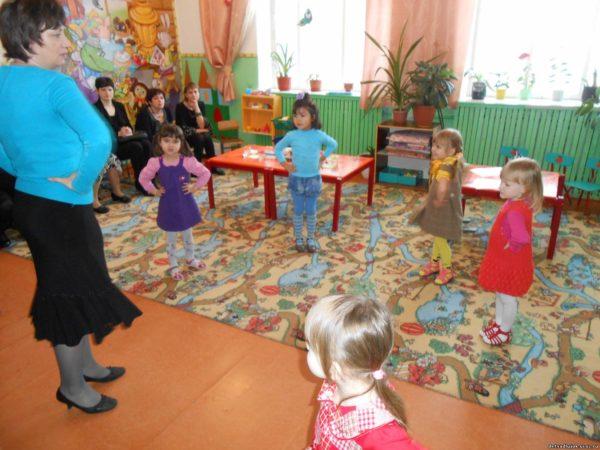 Воспитатель и дети стоят в кругу, выполняя упражнение
