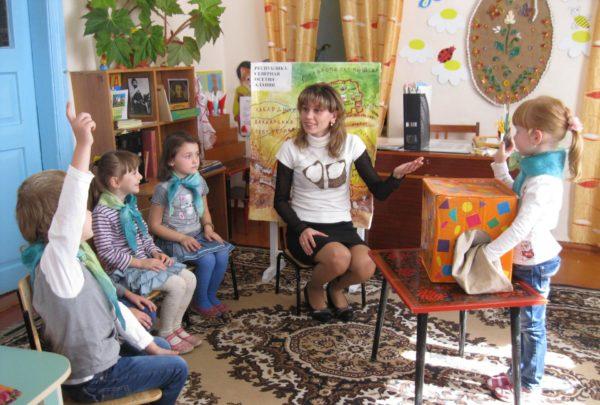 Девочка достаёт из яркой коробки предмет, воспитатель и дети наблюдают