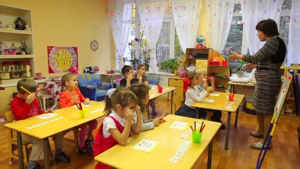 Педагог обращается к дошкольникам, сидящим за партами