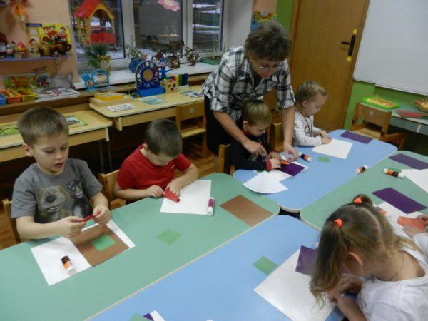 Дети выполняют поделки из бумаги, педагог помогает одному ребёнку