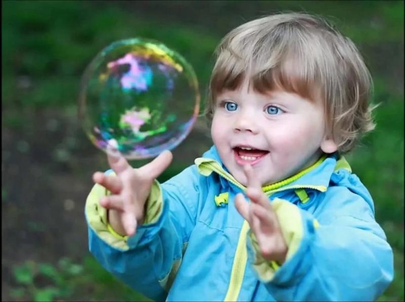 ребёнок рассматривает мыльный пузырь