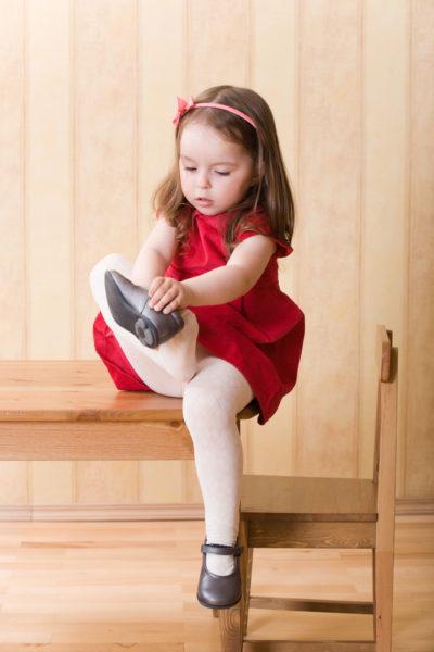 Девочка сама надевает туфли