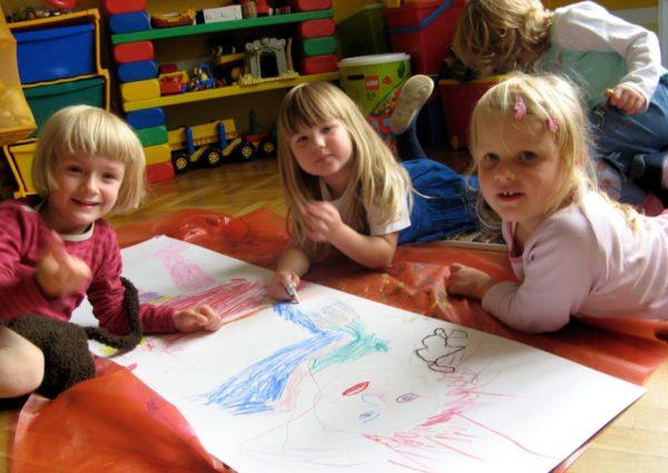 Три девочки, лёжа на полу, рисуют