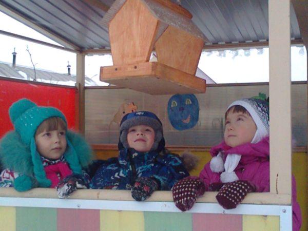 Трое детей наблюдают за кормушкой для птиц