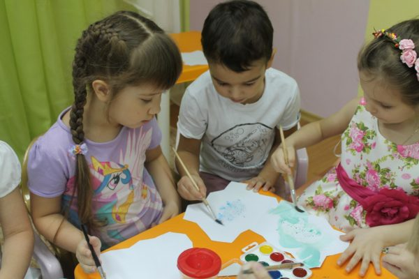 Трое детей рисуют красками