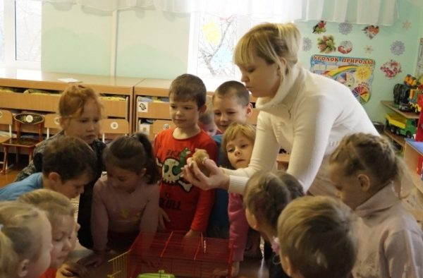 Педагог показывает воспитанникам хомячка