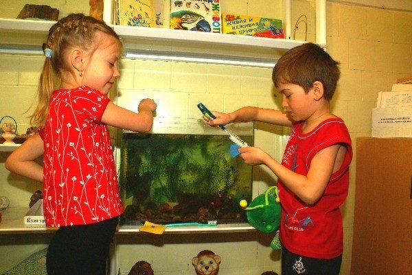 Мальчик и девочка ухаживают за рыбками в аквариуме