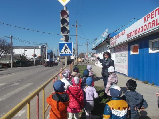 Воспитатель показывает дошкольникам светофор на улице