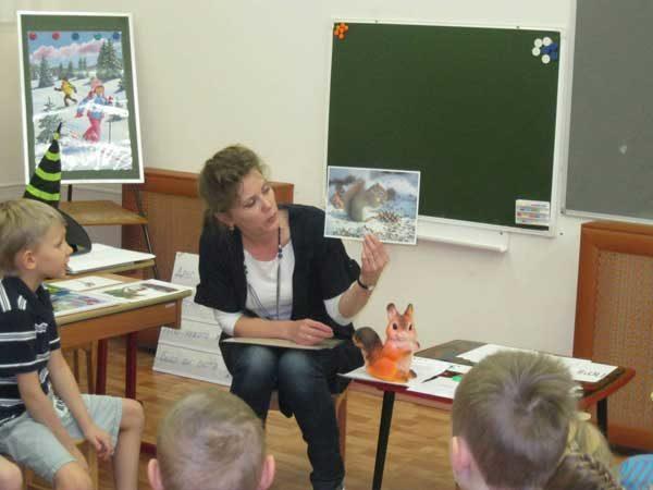 Воспитатель показывает детям картинки с изображением зимы