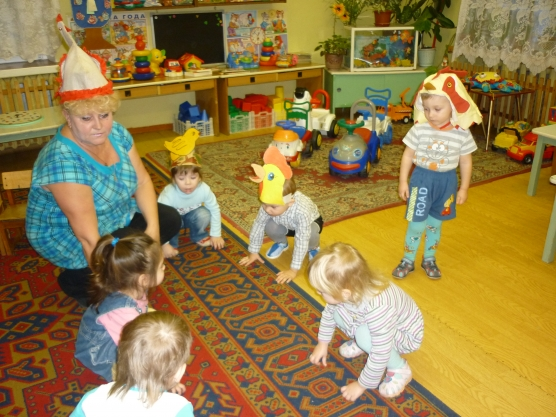 Воспитатель в шапочке курочки сидит на корточках с детьми-цыплятами