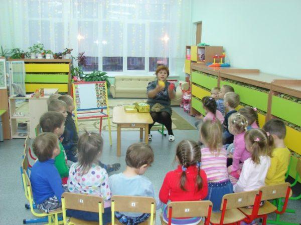 Воспитательница что-то говорит, показывая фрукты, дети слушают, сидя по кругу на стульях