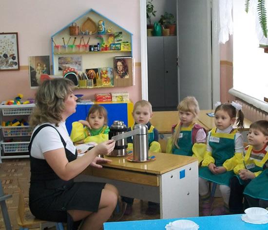 Воспитательница что-то рассказывает сидящим на стульях детям в зелёных фартуках