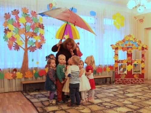 Воспитательница держит зонт и что-то рассказывает детям