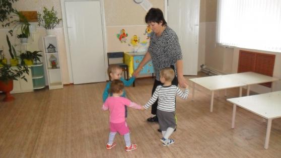 Воспитательница идёт в хороводе с тремя детьми
