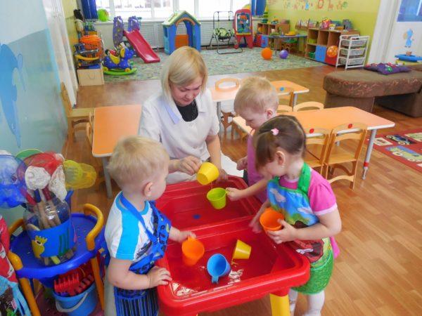 Воспитательница и дети черпают воду пластмассовыми кружками из двух тазиков