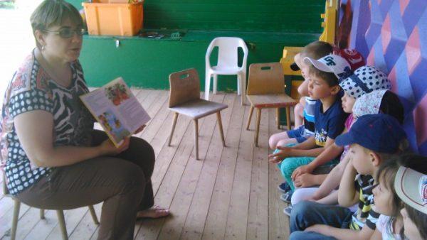 Воспитательница показывает сидящим на стульях детям книжку с картинками