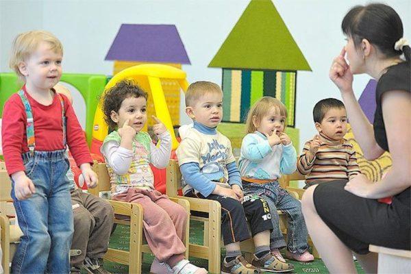 Воспитательница рассказывает детям сказку, показывая на нос