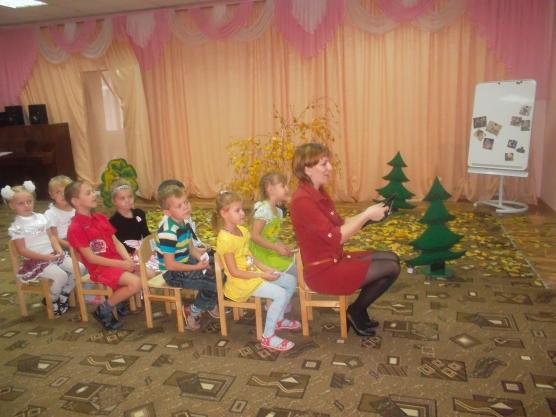 Воспитательница с детьми сидят паровозиком на стульях, на заднем плане — антураж леса