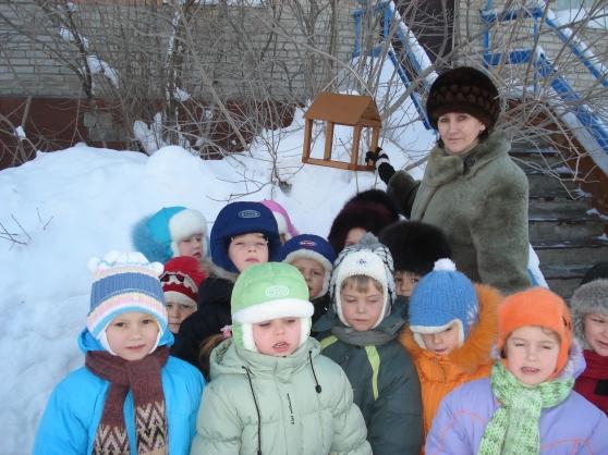 Дети и воспитательница стоят возле кормушки для птиц