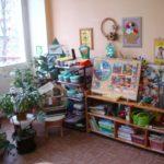 Стеллажи с материалами для опытов, календарём природы, аквариумом, рядом стоят горшки с комнатными растениями