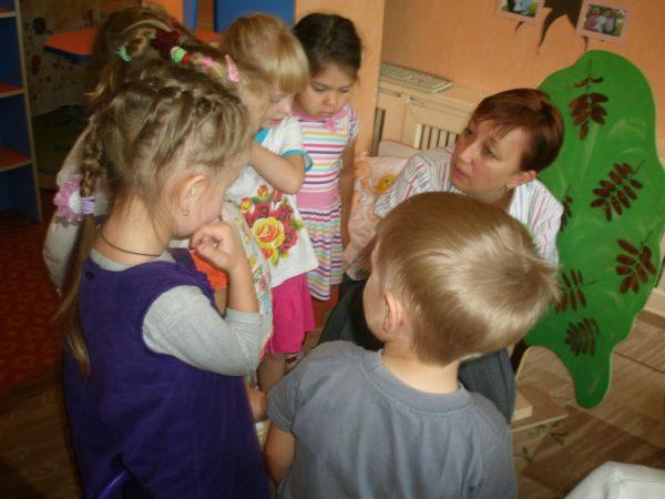 Воспитательница беседует с детьми, стоящими вокруг неё