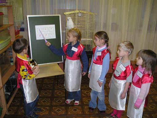 Дети в нарядных фартуках стоят у доски, одна девочка держит указку