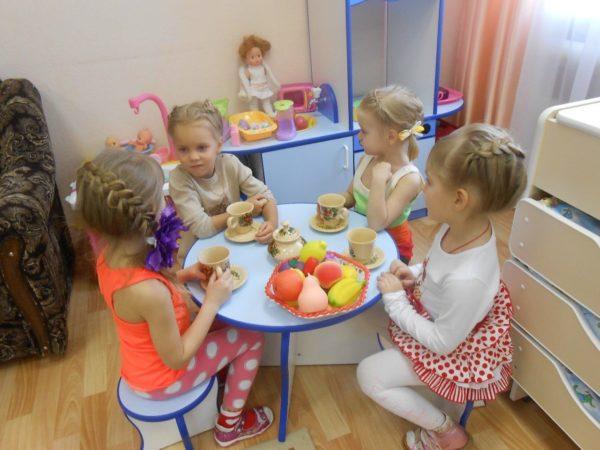 Девочки, сидя за столом с игрушечной посудой, играют в чаепитие
