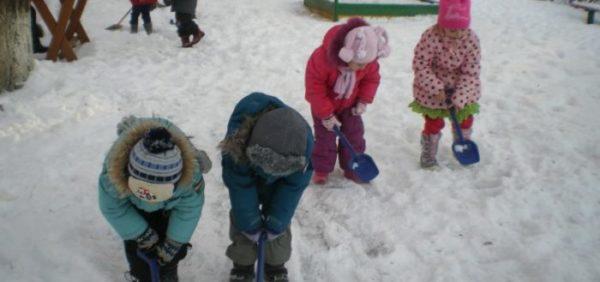 Четверо детей синими лопатками убирают снег