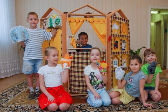 Четыре девочки и два мальчика с перчаточными куклами рядом с домиком-ширмой