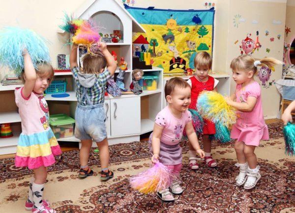 Четыре девочки и мальчик танцуют с султанчиками в помещении группы ДОУ
