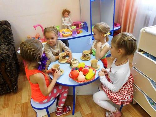 Четыре девочки сидят за столиком с фруктами и чашками