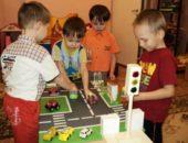 Четыре мальчика катают машинки по макету проезжей части со светофором