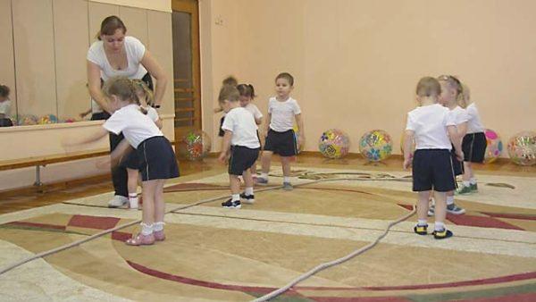 Дети бегают и прыгают вокруг двух верёвок, лежащих на полу