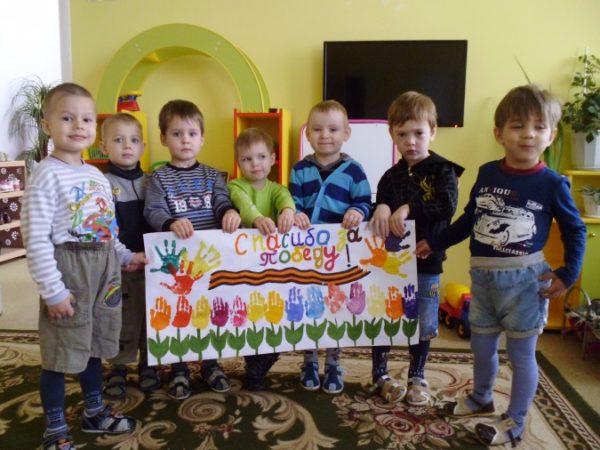 Дети держат нарисованный плакат, посвящённый Дню Победы