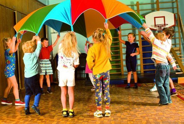 Дети держат разноцветный парашют в спортивном зале