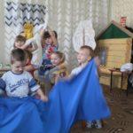 Дети держат в руках большой отрез синей материи, изображающей море