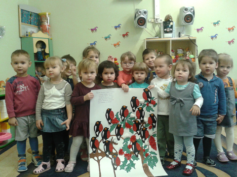 Дети держат ватман, на котором изображены деревья и стайка снегирей