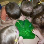 Дети дуют из трубочек в зелёный таз с мыльной водой
