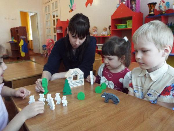 Дети и педагог разыгрывают сказку с помощью игрушек
