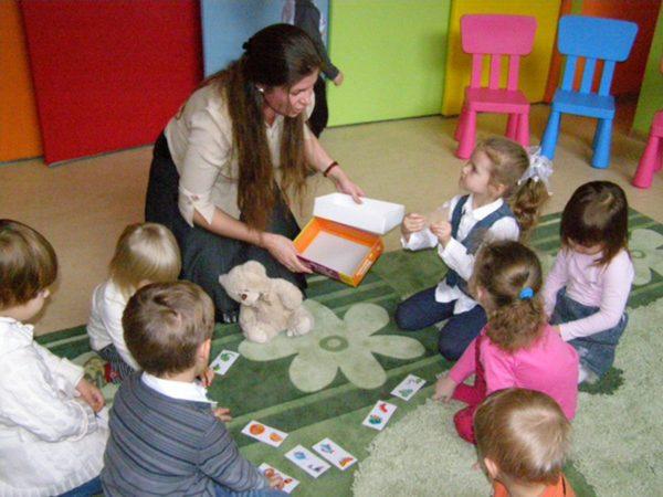 Дети и педагог сидят в кругу на ковре и играют в дидактическую игру