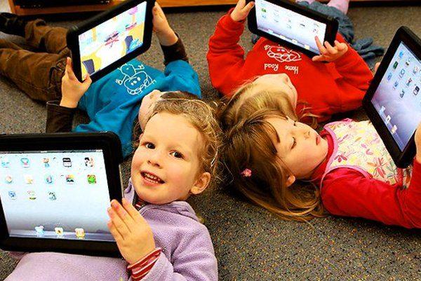 Дошкольники лежат на ковре с планшетами в руках