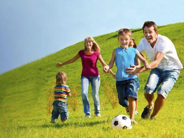 Дети и родители играют в мяч на природе