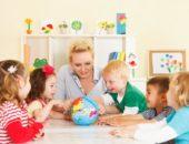 Дети и воспитатель рассматривают глобус
