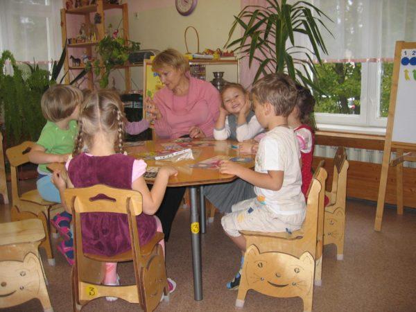 Дети и воспитатель сидят за столом, перед ними разложены дидактические материалы