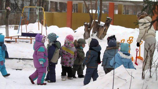 Дети и воспитательница на прогулке зимой, малыши подходят за лопатками для уборки снега