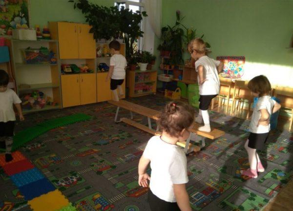 Дети идут по полосе препятствий из лавочки и коврика