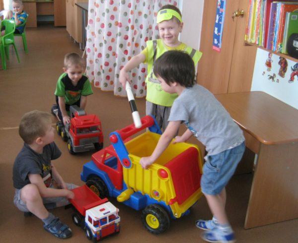 Мальчики играют с большими машинками, один ребёнок в костюме инспектора ДПС