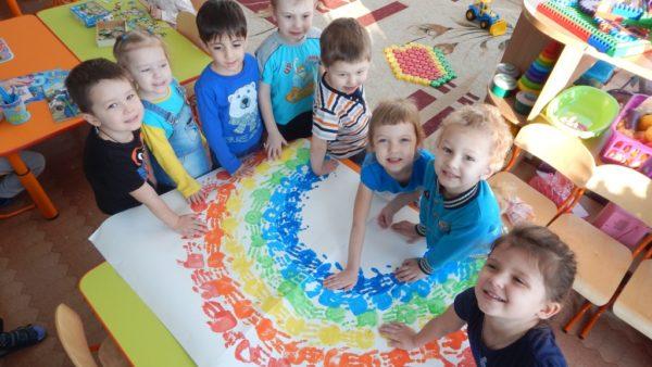 Дети из отпечатков ладошек делают рисунок радуги