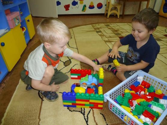 дети на коврике играют с конструктором