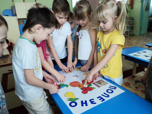 Дети рассматривают плакат с изображениями фруктов, лежащий на столе